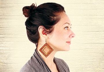 Jewelry artist Melissa Pare wearing her laser-etched earrings made from birch.