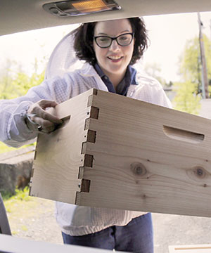 Jill McKenna Reed loads her Subaru Outback with beekeeping supplies.